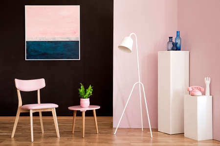 White lamp next to a table with plant and wooden chair in pastel living room interior with pink painting
