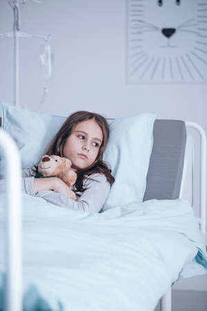 Lonely sad girl hugging plush toy while lying in a hospital bed
