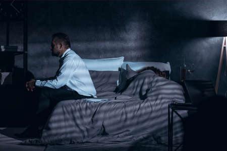 Dark gray room with a side view of a mature man sitting on a bed and having second thoughts after cheating and a woman sleeping under the cover