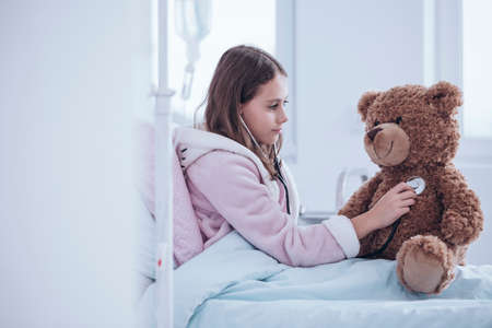 Sick girl with stethoscope examining teddy bear in the hospital bed