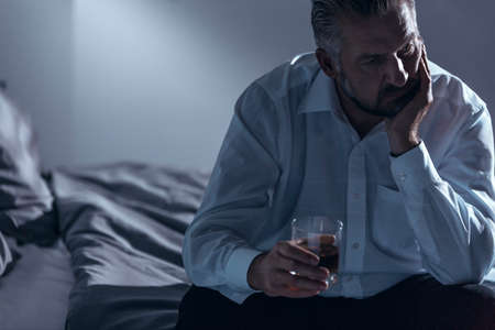 Close-up of a man with midlife crisis sitting on a bed with one hand on his chin and holding a glass of alcohol in the other