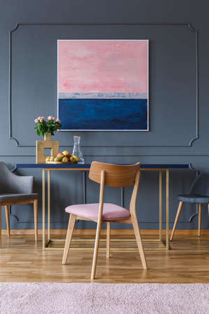 Pink wooden chair at table in dining room interior with painting on grey wall with molding