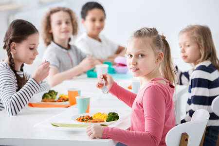 Girl eating vegetables with friends in the canteen during break at school