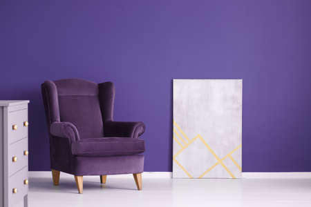 Grey poster next to suede purple armchair and cabinet in violet living room interior Banque d'images - 101667193
