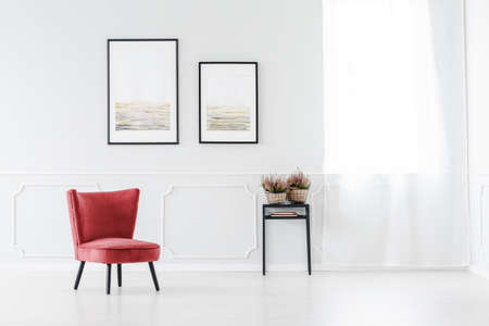 Elegant waiting room with red armchair standing against a white wall with molding in office interior