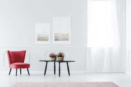Red, velvet armchair in bright living room interior with black table and wall with molding 版權商用圖片