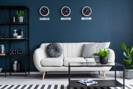 Elegant beige sofa in a dark, navy blue living room interior with black furniture and stylish decor