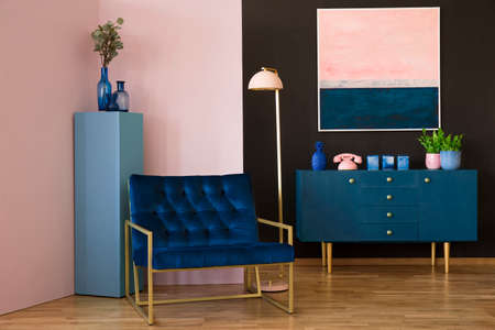 Navy blue armchair in modern living room interior with pink painting above cabinet