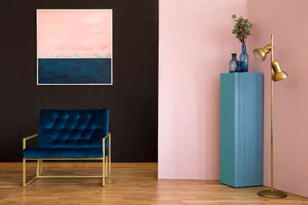 Navy blue armchair against black wall with pink painting in living room interior with gold lamp