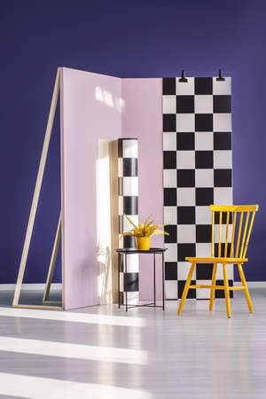 Yellow chair against checkerboard wall in purple photo studio interior with plant on table