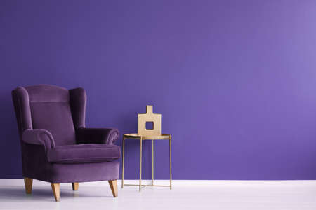 Vase on gold table next to a velvet purple armchair in minimal violet living room interior with copy space