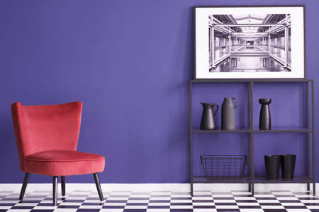 Black vases on shelves near red suede chair on checkerboard floor in violet flat interior with poster