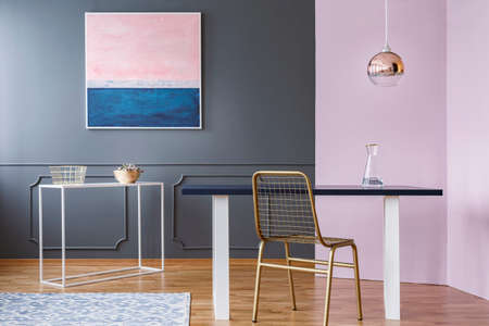 Gold chair at table under lamp in modern dining room interior with pink and blue painting Stock Photo