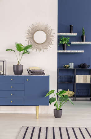 Sunburst mirror on a white wall, above a scandinavian style blue sideboard with golden elements in a stylish living room interior Stock Photo