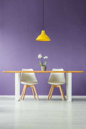 Symmetric, modern, minimal style interior with a front view of two white chairs behind a table with a flower in a pot and a yellow lamp against a purple wall Zdjęcie Seryjne