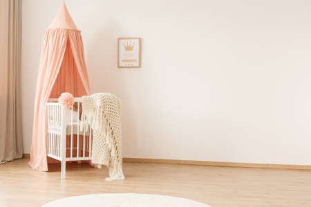 White woolen blanket and pastel pink pompom placed on a wooden crib with canopy in bright baby room interior with poster on the wall Stockfoto