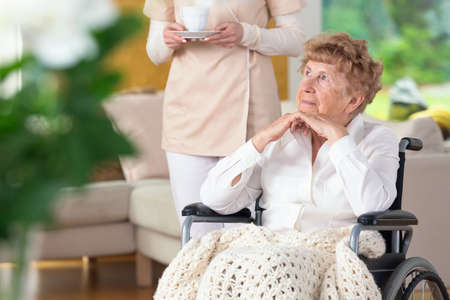 Thoughtful paralyzed elderly woman in a wheelchair and her caregiver Banque d'images - 104789012