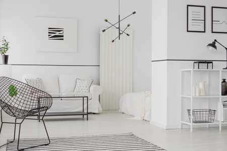 Modern black lamp hanging in open space flat interior with minimal posters and metal furniture