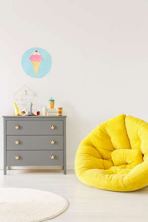 Yellow pouf next to a grey chest of drawers and ice-cream poster on a white wall in kid room interior. Place for your poster Stock Photo