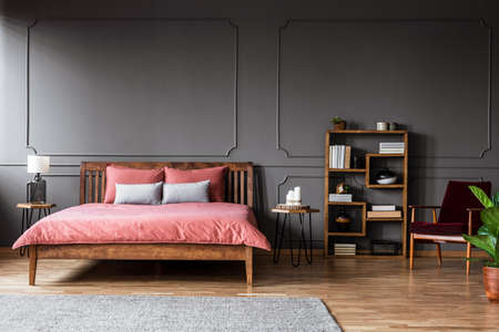 Real photo of a spacious bedroom interior with pink bed standing against black wall with molding next to a creative bookshelf and red armchair