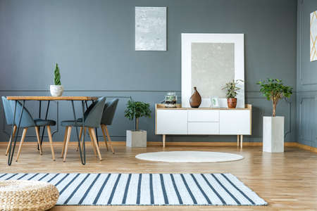 Modern painting standing on white cupboard with decor and fresh plants in grey dining room interior