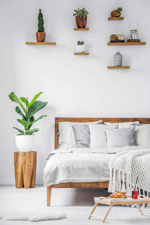 Breakfast tray standing on the floor beside a big comfortable bed with linen, blanket and pillows in a white bedroom interior. Real photo.