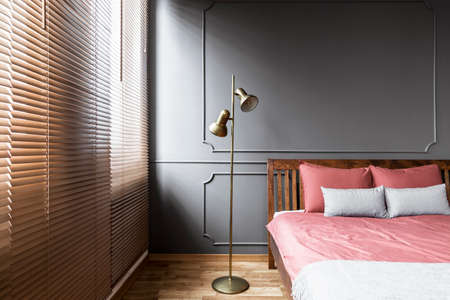 Blinds and golden lamp in dark and elegant bedroom interior with pink sheets on a wooden bed and molding on the wall. Real photo