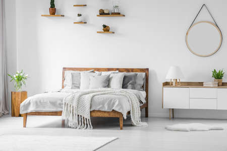 Comfortable, big, wooden bed with linen, pillows and blanket, nightstand beside and round mirror hanging on a white wall in a bright bedroom interior. Real photo. Reklamní fotografie