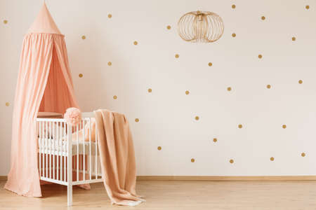 Dirty pink blanket thrown on white wooden crib with canopy in simple baby room interior with dotted wall
