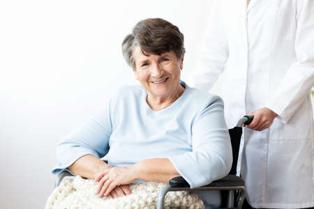 Smiling disabled senior woman in a wheelchair in the nursing house Stock Photo
