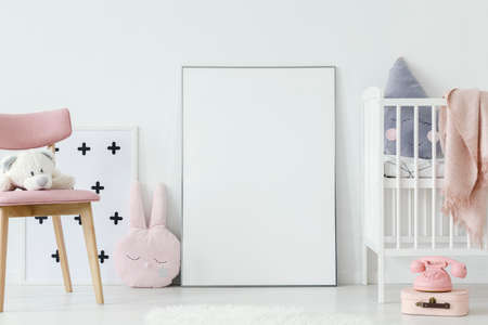 Plush toy on pink wooden chair next to empty poster with mockup in babys room interior. Real photo. Paste your poster here 版權商用圖片