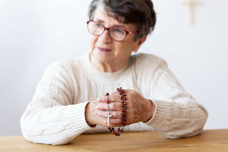 Religious senior woman holding red rosary with cross while praying. Focus on the hands