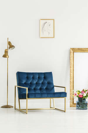 A luxurious, navy blue armchair, golden elements,framed art and a colorful flowers bouquet in a white living room interior