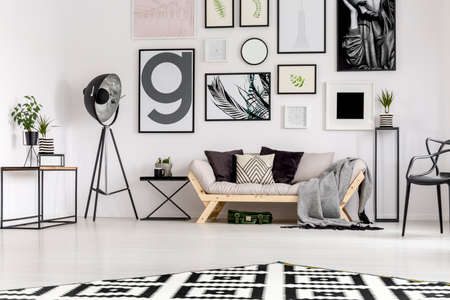 Lamp next to beige couch with pillows in scandi living room interior with gallery of posters