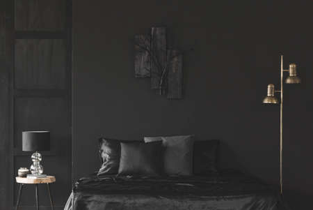 Gold lamp next to bed in black bedroom interior with sculpture on dark wall
