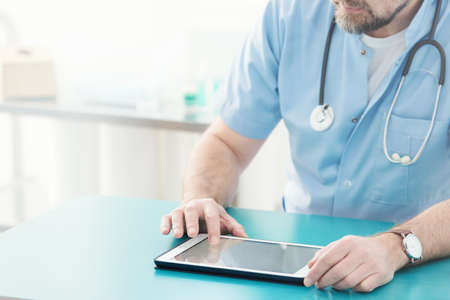 Close-up of doctor with stethoscope using tablet during work