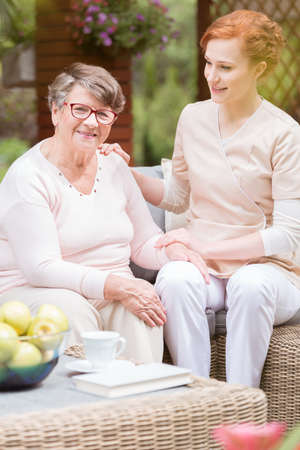Tender professional caregiver in uniform putting her hand on a shoulder of an elderly woman during snack time on a patio of a senior home. Blurred background.