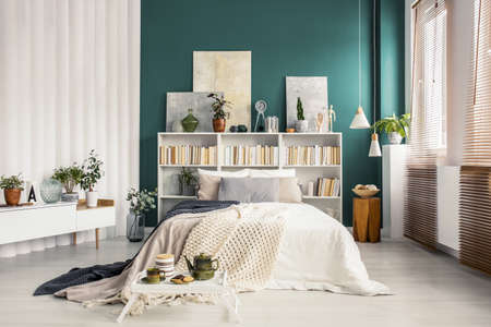 Bookcase headboard with artworks and decorations in a stylish turquoise green bedroom interior with white furniture