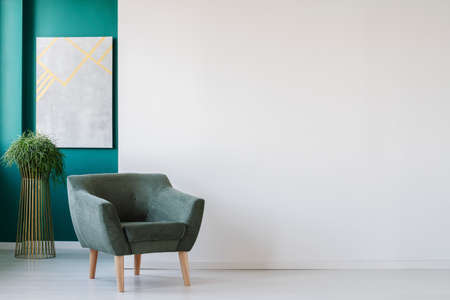 Minimalist living room interior with empty, white wall, green armchair, plant and painting