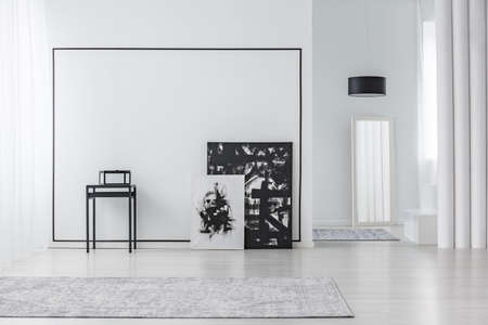 Black and white painting in minimal living room interior with grey carpet and mirror Stockfoto
