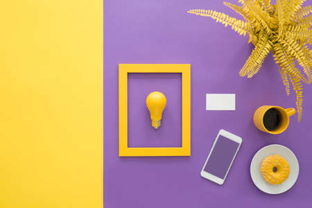 Copy space on yellow background next to a lightbulb in frame near mockup of smartphone on violet desk 版權商用圖片