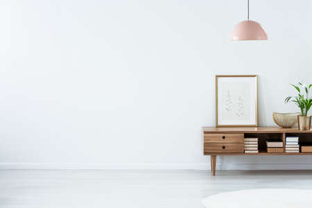 Retro pink ceiling lamp above a wooden sideboard in a modern living room interior with an empty white wall and copy space. Place for your sofa
