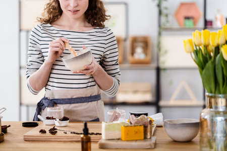 Nahaufnahme einer Frau, die organische Gesichtscreme mit Schokolade in einer Schüssel macht