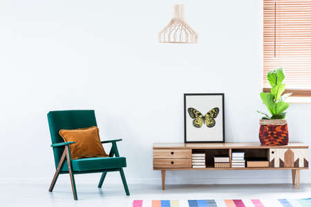 Scandinavian sideboard with books and colorful decorations and a retro armchair in a white living room interior