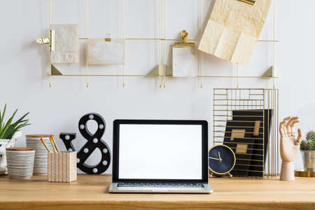 Mockup of laptop on wooden desk with clock, plants and pots in workspace interior 版權商用圖片
