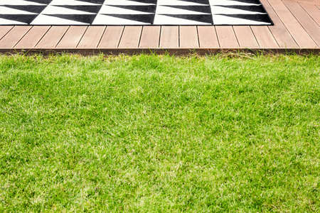 Green grass and a wooden terrace with geometrical rug in a garden Stock Photo