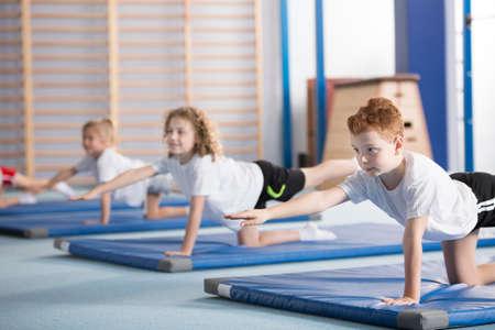 Ragazzo della scuola elementare e altri bambini che esercitano una posizione yoga sul tavolo di bilanciamento durante la lezione di ginnastica extracurricolare per aiutare con la postura e la forza del corpo centrale