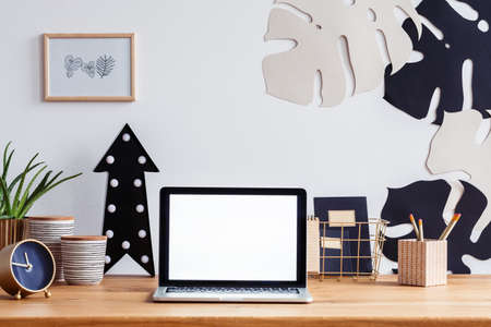 Mockup of laptop on wooden desk with gold clock and black arrow in home office interior