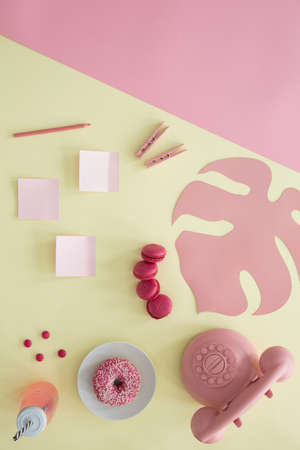 Doughnut between pink phone and bottle on yellow background with sticky notes, clips and cookies Stock Photo