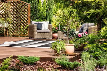 Wiklinowe meble ogrodowe na tarasie ozdobionym roślinami, krzewami, kwiatami i drzewami